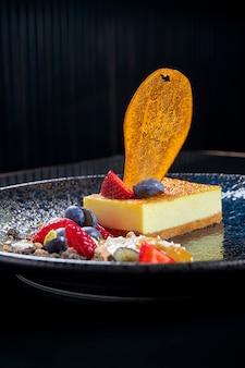 Traditionele cheesecake uit new york met bosbessen, aardbeien en gekarameliseerde peer in een zwarte keramische plaat. stijlvol restaurant serveren. geserveerd dessert