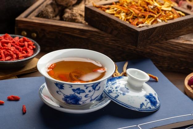 Traditionele chinese gezondheidsthee en klassieke medische boeken op tafel