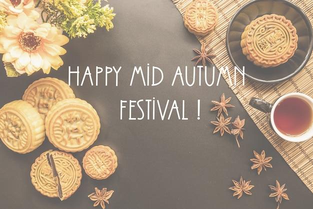 Traditionele chinese mid herfst festival eten mooncakes op zwarte achtergrond met thee, kruiden en bloemen plat lag, woorden happy mid autumn festival