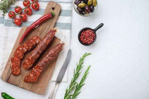 Traditionele chorizo bezuinigingen met kruiden en ingrediënten op wit met ruimte voor tekst