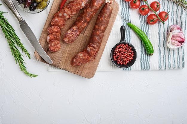 Traditionele chorizo snijdt met kruiden en ingrediënten op een witte ondergrond, bovenaanzicht met kopie ruimte.