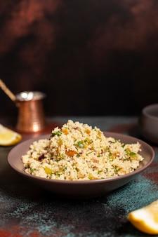Traditionele couscous met groenten en kruiden in een kom. levantijnse vegetarische salade. libanese, arabische keuken. detailopname. kopieer ruimte