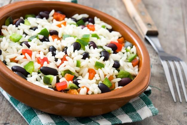 Traditionele cubaanse rijst, zwarte bonen en peper op houten tafel oppervlak. moros y cristianos.