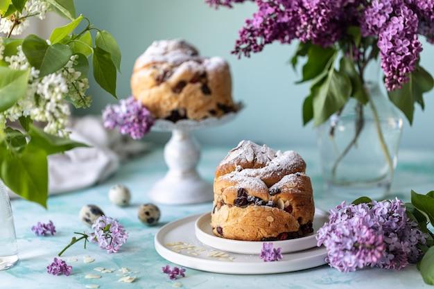 Traditionele cupcake pasen cake kraffin met rozijnen en poedersuiker op tafel. pasen taarten, kaarsen en een boeket van lila bloemen.