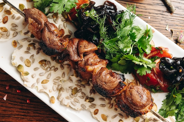 Traditionele eend sjasliek op een barbecue spies op witte plaat