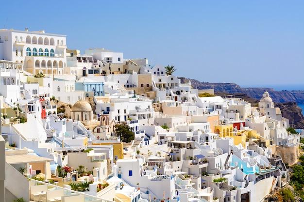 Traditionele en beroemde huizen en kerken met blauwe koepels over de caldera, egeïsche zee