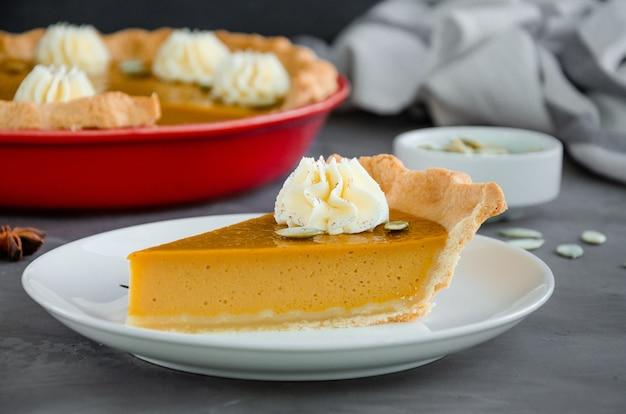 Traditionele feestelijke pompoentaart met kruiden slagroom en zaden dessert voor thanksgiving