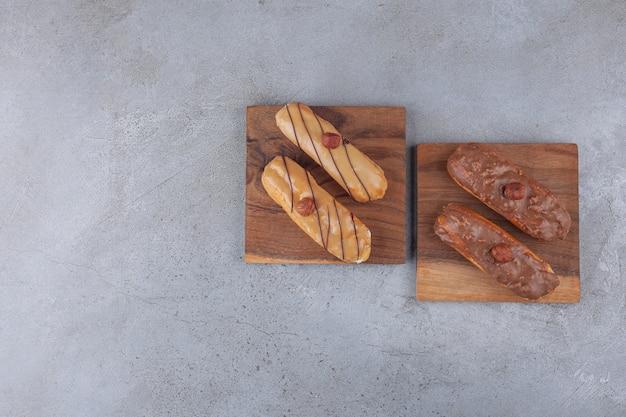 Traditionele franse eclairs met chocolade op een houten bord.