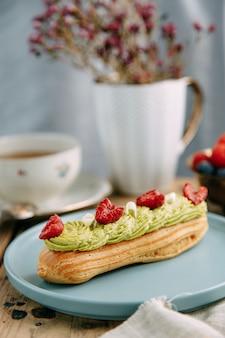 Traditionele franse eclairs met room. eclairs versierd met chocolade en bessen op een bord.