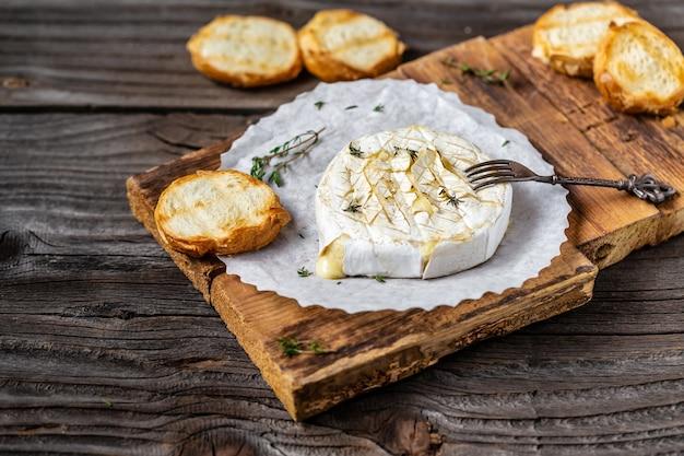 Traditionele franse huisgemaakte gebakken camembert kaas met tijm en stokbrood.