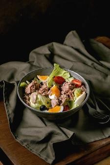Traditionele franse nicoise salade met ingeblikte tonijn, olijven en eieren, geserveerd in keramische kom op donker linnen tafelkleed op houten tafel. donkere rustieke stijl