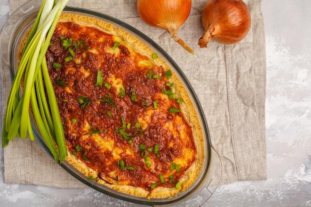 Traditionele franse uientaart. quiche lotharingen met ui, kaas en eieren in een glasovenschotel, hoogste mening