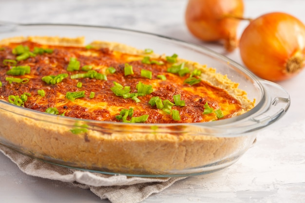 Traditionele franse uientaart. quiche lotharingen met ui, kaas en eieren in een glazen ovenschaal.