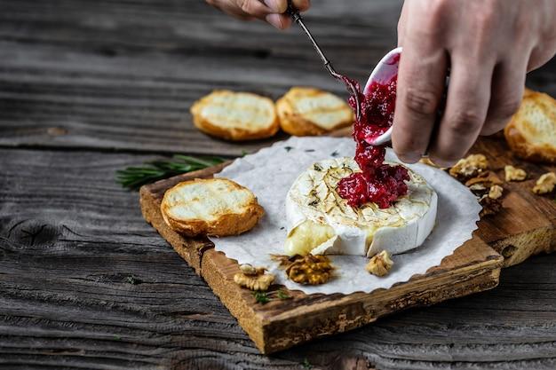 Traditionele franse zelfgemaakte gebakken camembert-kaas. cranberrysaus wordt uit een kan over kaas gegoten.