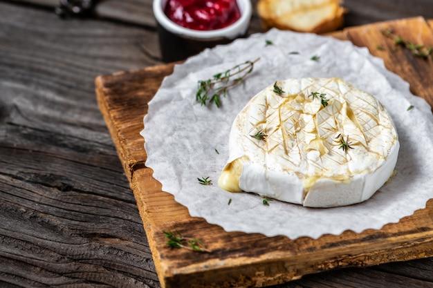 Traditionele franse zelfgemaakte gebakken camembert-kaas met tijm en stokbrood op houten tafel.