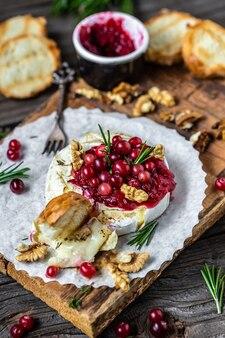 Traditionele franse zelfgemaakte gebakken camembert met toast, rozemarijn, veenbessen en noten op rustieke houten tafel.