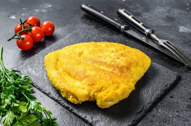 Traditionele gebakken kipschnitzel. zwarte achtergrond. bovenaanzicht.