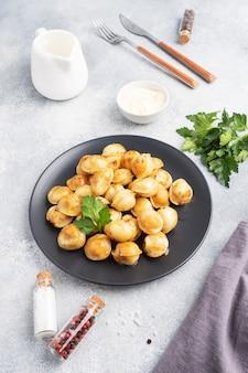 Traditionele gebakken pelmeni, ravioli, dumplings gevuld met vlees op zwarte plaat, russische keuken. grijze betonnen tafel, kopie ruimte.