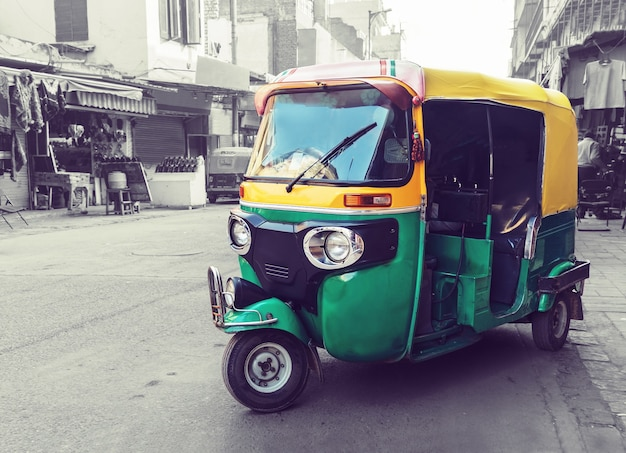 Traditionele geelgroene tuk tuk-taxi op straat. indiaas openbaar vervoer in de straten van new delhi. driewieler vintage retro motorfiets 50-60 jaar 20e eeuw