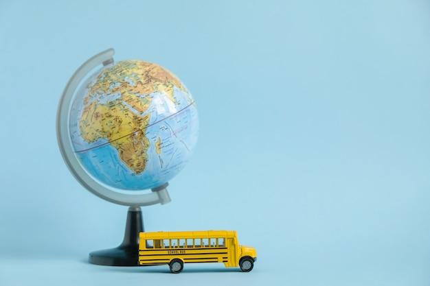 Traditionele gele schoolbus en wereldbol op blauw