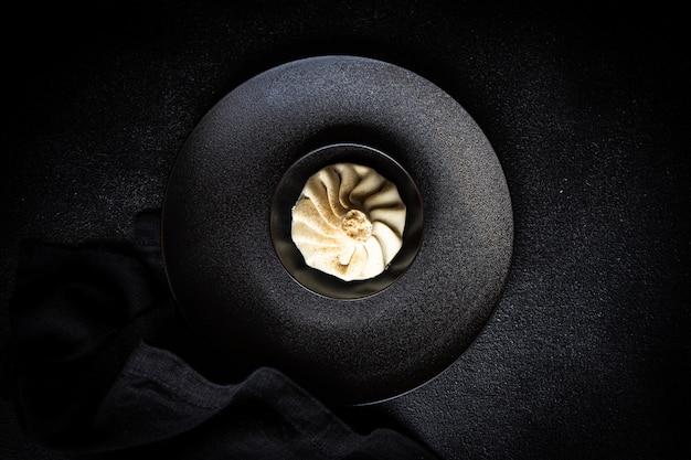 Traditionele georgische demping bekend als khinkali in het georgisch op zwarte plaat, geserveerd met zwart servet op zwart beton met kopie ruimte