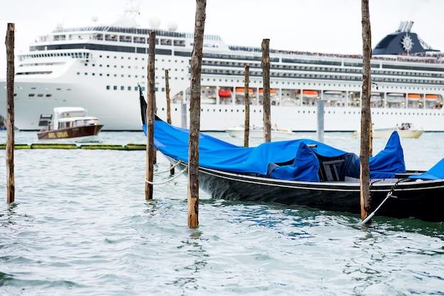 Traditionele geparkeerde gondelboot op een achtergrond van het moderne cruiseschip van de reisluxe