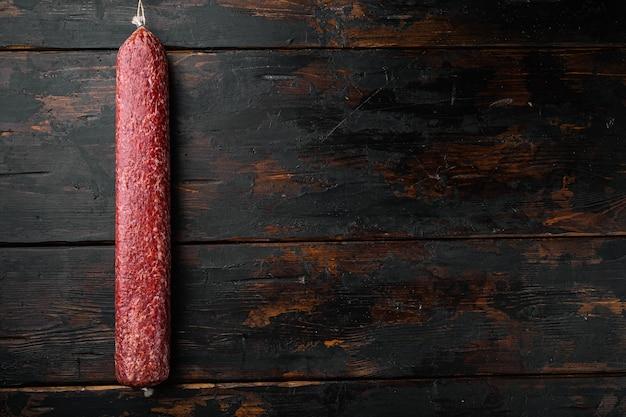 Traditionele gerookte salami worst set, op oude donkere houten tafel, bovenaanzicht plat lag