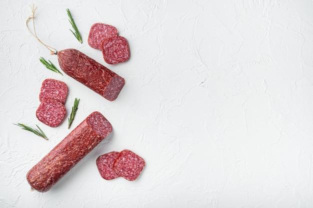 Traditionele gerookte salamiworst met kruidenset, op witte stenen tafel, bovenaanzicht plat gelegd