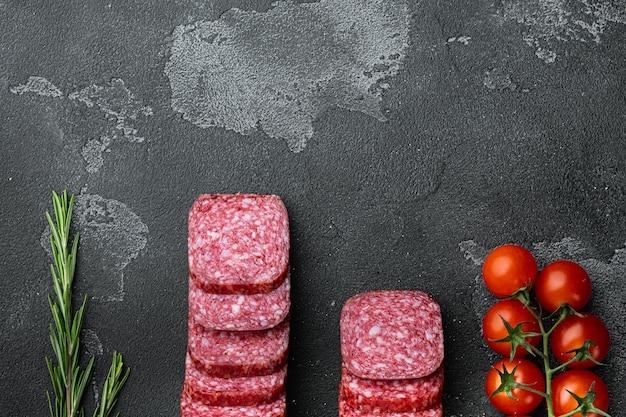 Traditionele gerookte salamiworst met kruidenset, op zwarte donkere stenen tafel, bovenaanzicht plat gelegd