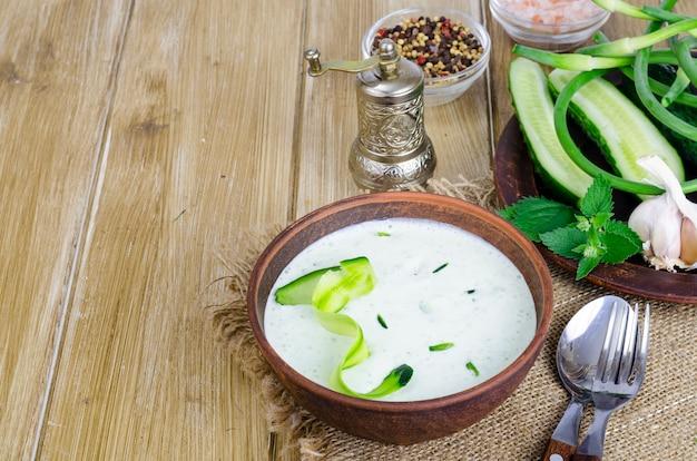 Traditionele griekse dip saus of dressing tzatziki bereid met geraspte komkommer, yoghurt, olijfolie en verse dille op houten tafel in keramische kom.