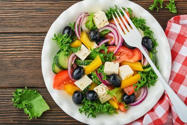 Traditionele griekse salade van verse komkommer, tomaat, paprika, sla, rode ui, fetakaas en olijven met olijfolie op wit bord. gezonde voeding, bovenaanzicht.