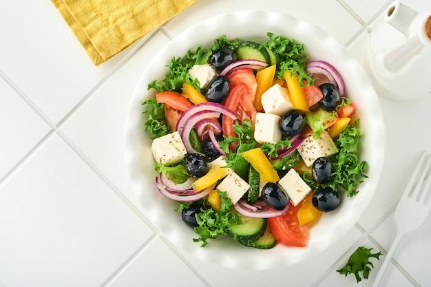 Traditionele griekse salade van verse komkommer, tomaat, paprika, sla, rode ui, fetakaas en olijven met olijfolie op witte plaat. gezonde voeding, bovenaanzicht.