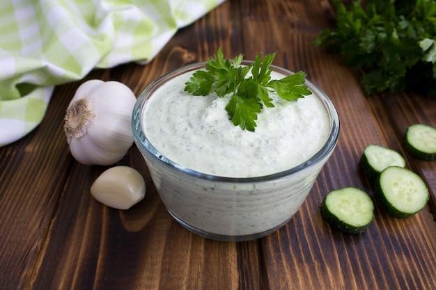 Traditionele griekse yoghurt met komkommer op de bruin houten tafel