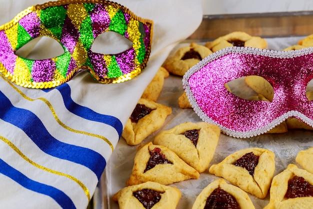 Traditionele hamantaschen joodse koekjes met jam, talliet en masker voor purim