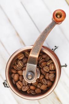 Traditionele handmatige koffiemolen of braammolen op witte rustieke planken
