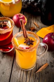 Traditionele herfst- en winterdranken en cocktails. witte en rode herfst hete kruidige sangria met anijs, kaneel, appel, sinaasappel, wijn. in glazen mokken, oude rustieke houten tafel. selectieve focus kopie ruimte
