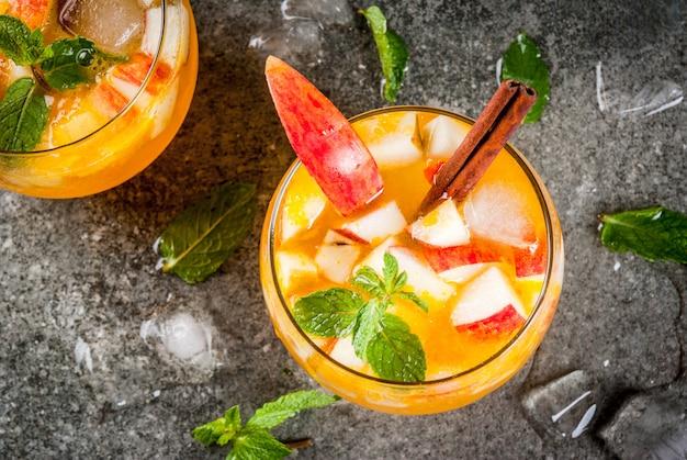 Traditionele herfstdranken, appelcider mojito-cocktails met munt, kaneel en ijs. op zwarte stenen tafel, bovenaanzicht