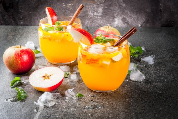 Traditionele herfstdranken, appelcider mojito-cocktails met munt, kaneel en ijs. op zwarte stenen tafel, kopie ruimte