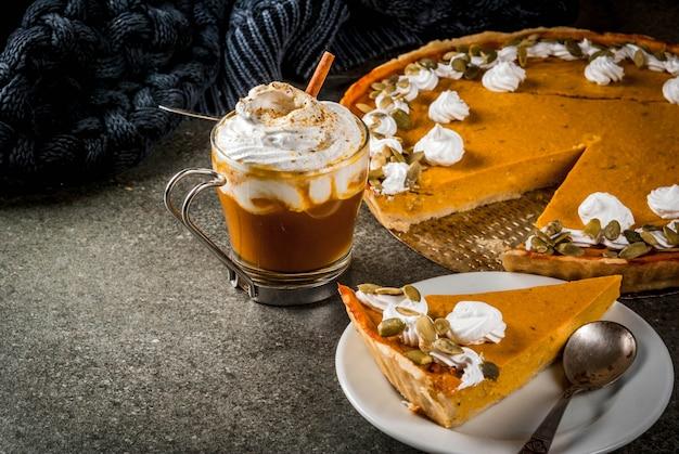 Traditionele herfstgerechten. halloween, thanksgiving. pittige pompoentaart met slagroom en pompoenpitten, pompoen latte met kaneel op zwarte stenen tafel met deken. copyspace