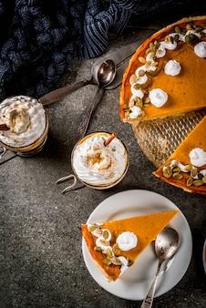 Traditionele herfstgerechten. halloween, thanksgiving. pompoentaart, met slagroom en pompoenpitten, pompoen latte met kaneel op zwarte stenen tafel met deken. kopieer ruimte bovenaanzicht