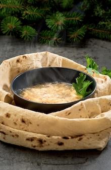Traditionele hete khash soep in een kom, stoom stijgt boven de schotel, close-up. traditionele armeense, kaukasische oosterse keuken - khash, met verse kruiden, knoflook en gedroogd lavashbrood