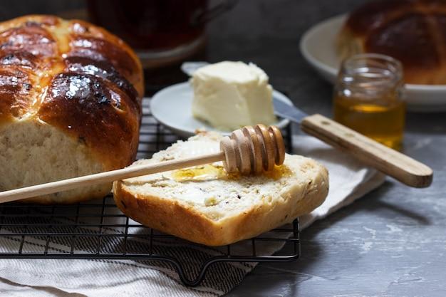 Traditionele hete kruisbroodjes met honing en boter op een concrete achtergrond.