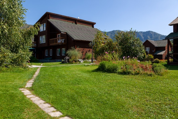 Traditionele houten huisjes op zonnige dag op het platteland met groen gazon, bloemen