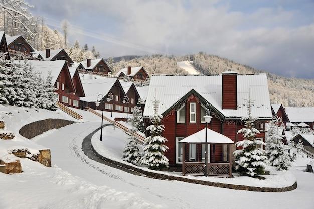 Traditionele houten huizen op een heuvelhelling in de bergen van de karpaten, omgeven door met sneeuw bedekte sparren.