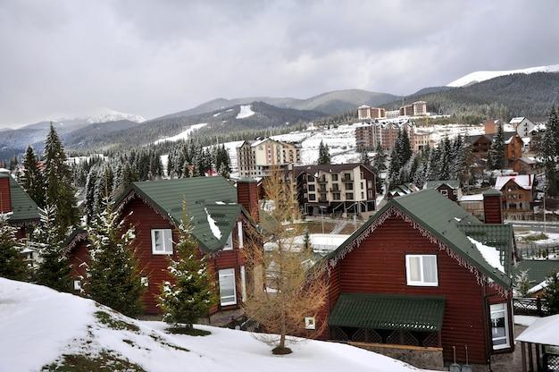 Traditionele houten huizen op een heuvelhelling in de bergen van de karpaten, omgeven door sparren.