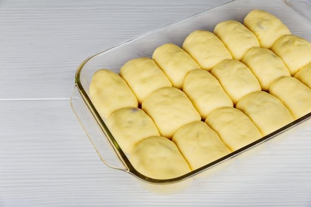 Traditionele huisgemaakte cake met kwark en pruimenjam die cakevorm invult, voor het bakken,