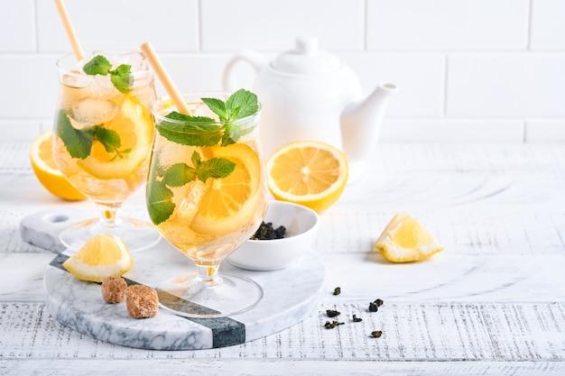 Traditionele ijsthee met citroen en ijs in hoge glazen op marmeren tafel achtergrond ijsthee met citroen. selectieve aandacht. verfrissing koude zomerdrank.
