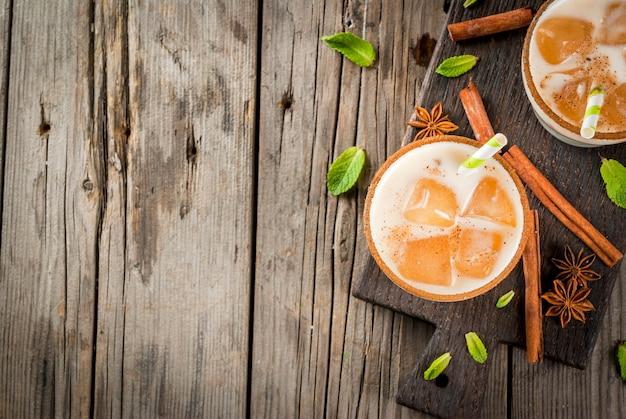Traditionele indiase drank is ijsthee of chai masala, met ijsblokjes van chai, melk en muntblaadjes. met gestreepte rietjes, op een houten bord. op een oude rustieke houten tafel. kopieer ruimte bovenaanzicht