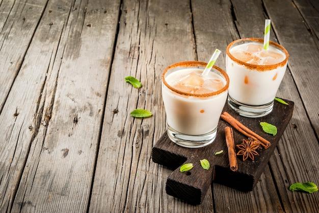 Traditionele indiase drank is ijsthee of chai masala, met ijsblokjes van chai, melk en muntblaadjes. met gestreepte rietjes, op een houten bord. op een oude rustieke houten tafel. kopieer ruimte