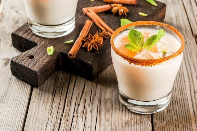 Traditionele indiase drank is ijsthee of chai masala, met ijsblokjes van chai, melk en muntblaadjes. met gestreepte rietjes, op een houten bord. op een oude rustieke houten tafel.
